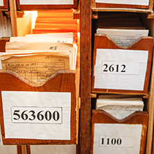 A picture showing a collection of old documents, photos, and/or artifacts next to an archival box