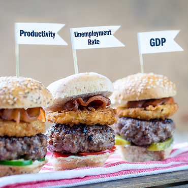photo illustration of three hamburger sliders topped with small, white flags labeled productivity, unemployment rate, and GDP