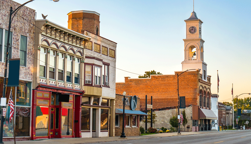 photograph of storefront buildings along a small town street at sunset