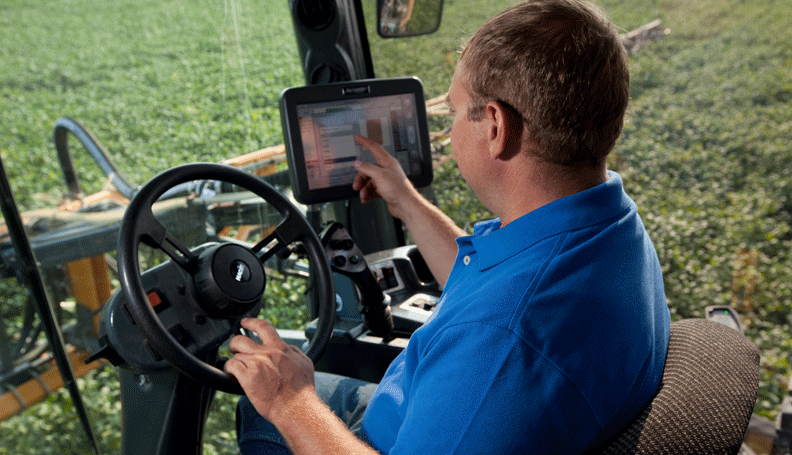 farmer inside tractor pointing at touchscreen