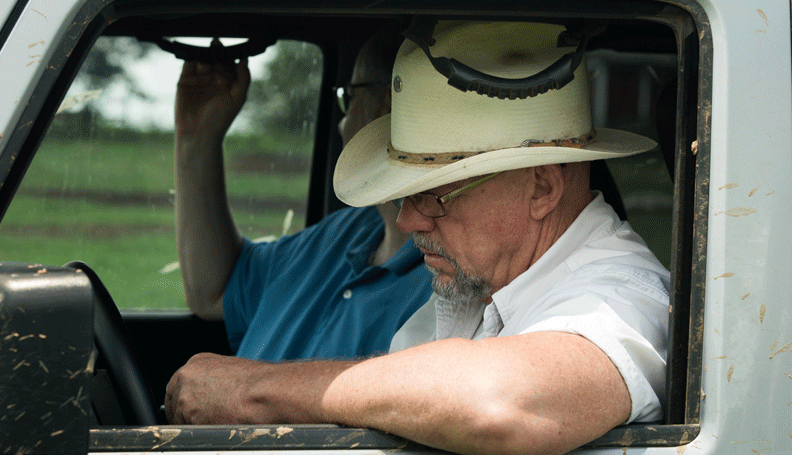 Will Harris of White Oak Pastures Farm sits in his Jeep with a coworker
