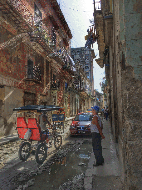 photo of narrow Cuban city street as a man looks at a passing foot taxi