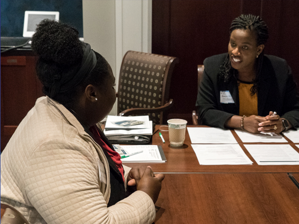 an Atlanta Fed employee talking with another person at a desk