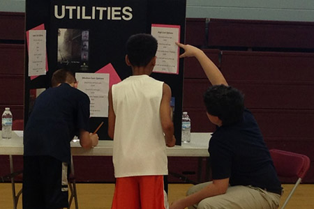 A student from Daniel McKee Alternative School points out utility options to students participating in the Reality Fair.