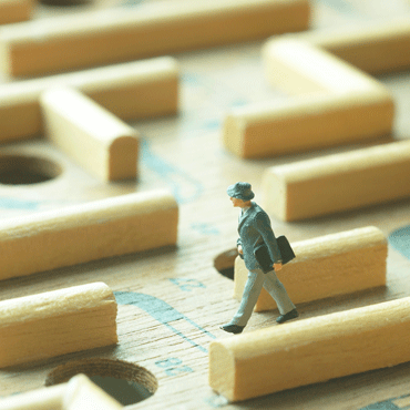 miniature business man walking through wooden pegs maze