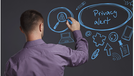 man in a blue dress shirt drawing blue icons and symbols related to privacy on a blackboard