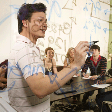 person writing on a glass board in front of a group of people