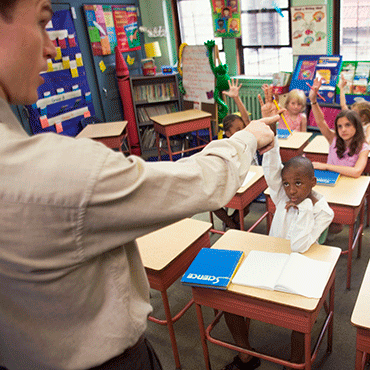 a male teacher in the foreground pointing as if to call on a particular student when all students have their hands raised