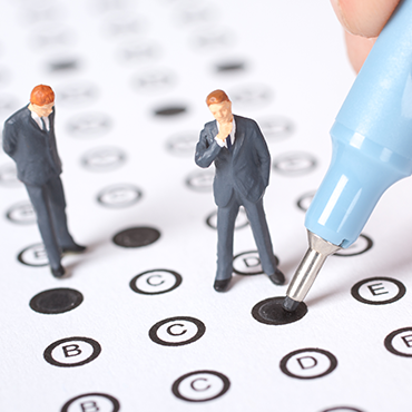 closeup photo showing a pair of miniature figures on top of a test form being filled out with a blue pencil