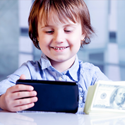 photograph of a smiling young boy holding a phone and a stack of bills