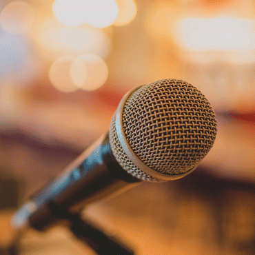 Photo of a microphone with audience blurred out