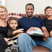 family of 4 sitting on couch with book open