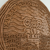 Embossed clay Atlanta Fed seal with the Atlanta Fed column and Federal Reserve mission statement.
