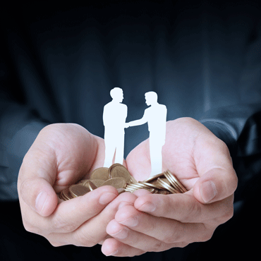 two miniature white silhouettes of people standing on pile of coins cupped in outstretched hands