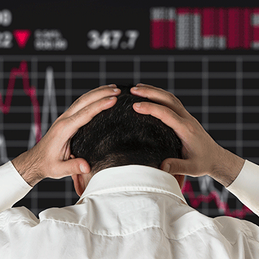 man from behind clasping head with stock market display in background