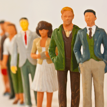 figurines of diverse group of people losely standing in line