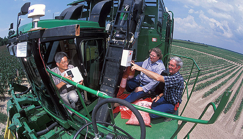 three farmers sitting atop a large harvester