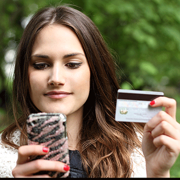 female facing viewer holding mobile phone in one hand and credit or debit card in the other