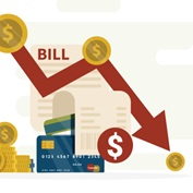 gold dollar coins and credit cards in front of a bill on a chart with arrow descending