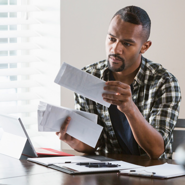 man with computer open while sorting checks or bills