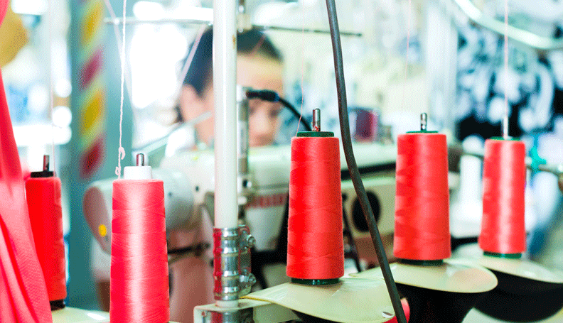 a clothing factory with red spools of thread in the foreground and a female worker in the background