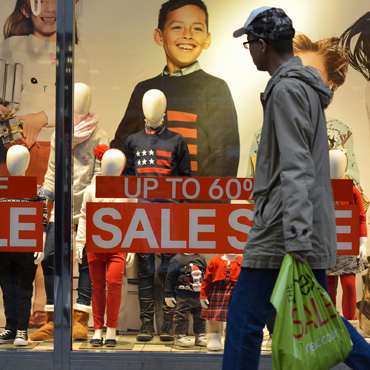 man walking by a retail clothing store display window with banners indicating sale