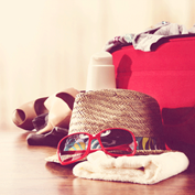 photograph of a summer hat, sunglasses, shoes, and other travel gear on the floor next to a redsuitcase