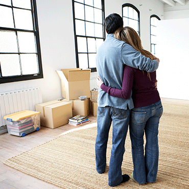 couple embracing in loft home setting and are either moving in or out