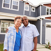 senior african american couple embracing in yard in front of house