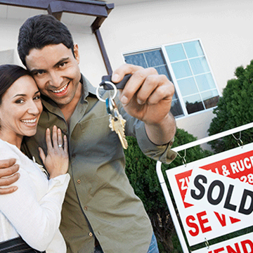 couple embracing and standing in front of sold sign as one holds up house keys to the viewer