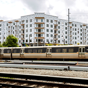 photograph of a MARTA train passing in front of a new housing development under construction