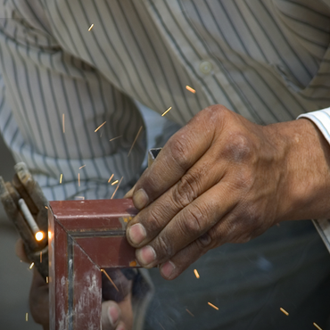 close up of two hands welding the corner of some type of frame or brace