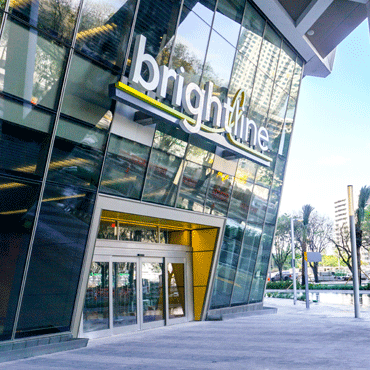 entrance to new glass front building with high rise under construction in background