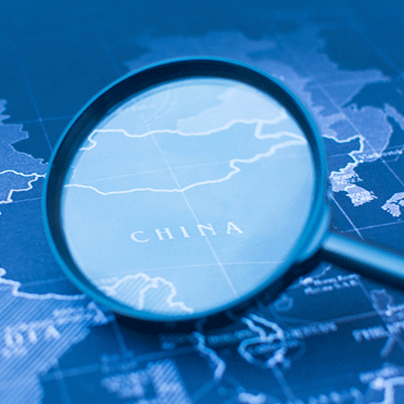 Photo of a magnifying glass highlighting China on a globe with blue tone