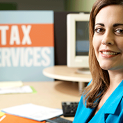 woman facing viewer with out of focus banner in background reading tax services