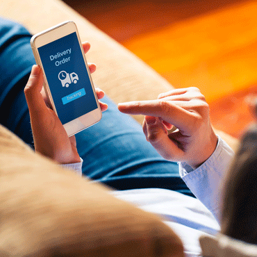 person sitting on couchwith finger poised to trigger a delivery order on a smart phone
