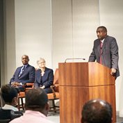 Andre Anderson at a podium during the announcement to staff of his his first vice presidency. Sitting his left aside are Raphael Bostic and Marie Gooding.
