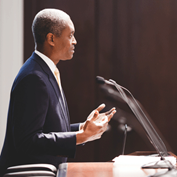 in profile, Raphael Bostic, president and CEO of the Federal Reserve bank of Atlanta, speaking at a podium as viewed from his left side