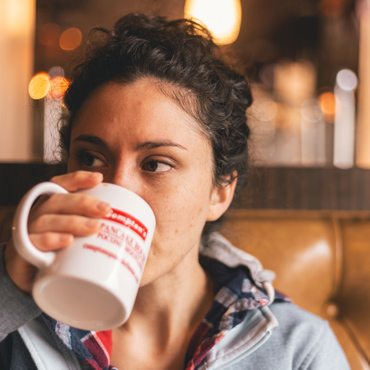 woman holding coffee cup up to mouth to drink
