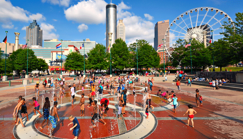 people playing in the fountains of Atlanta's Centennial Olympic Park on a bright summer day