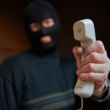 man with a mask on holding a phone