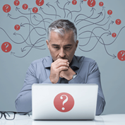 photo illustration of a middle-aged man sitting before a laptop with arrows and question marks in red circles around his head