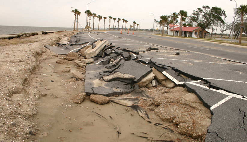 photograph of a seaside road buckled and collapsed from a severe storm