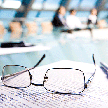 reading glasses over document in foreground in the background are out-of-focus people seated around an executive conference table
