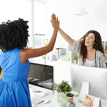 two women giving each other a high five over a cubicle divider