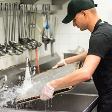 photograph of a worker rinsing a sheet pan in a restaurant kitchen