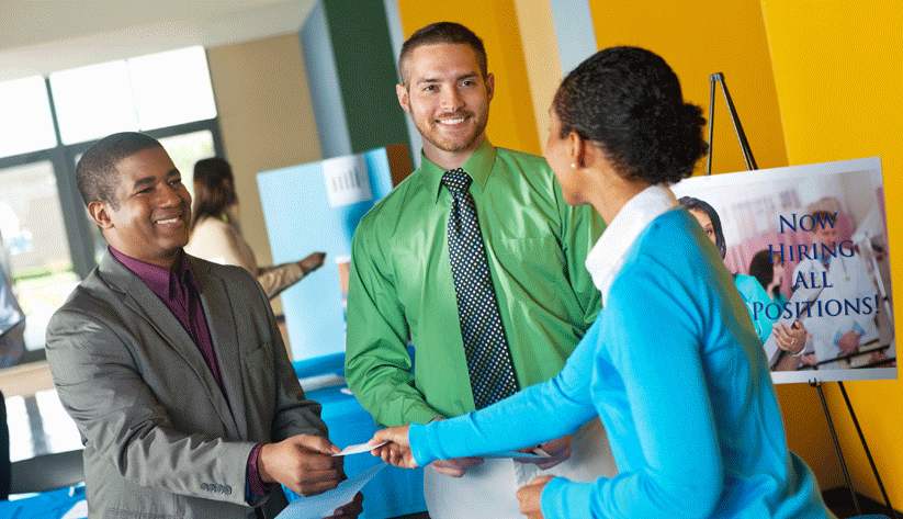 photograph of two men and one woman exchanging business cards at a job fair