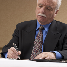 photo of man signing a document