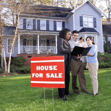 photo of realtor and couple next to for sale sign