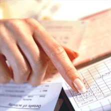 photo of woman's hand pointing to check register entry